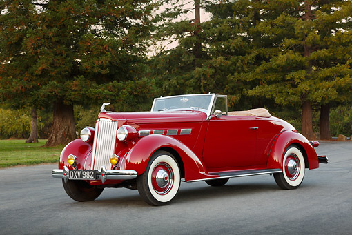 AUT 19 RK1058 01 © Kimball Stock 1937 Packard 120 Convertible Coupe Red 3/4 Front View On Pavement By Trees