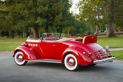 AUT 19 RK1060 01 © Kimball Stock 1937 Packard 120 Convertible Coupe Red 3/4 Rear View On Pavement By Trees