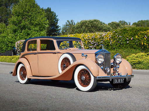 AUT 19 RK1067 01 © Kimball Stock 1937 Rolls-Royce 25/30 James Young Saloon Tan 3/4 Front View On Pavement By Shrubs