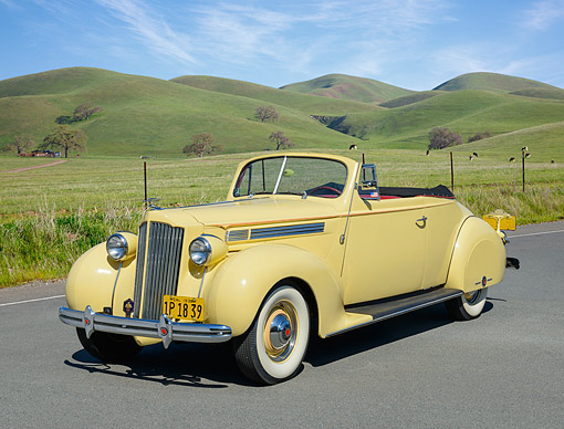 AUT 19 RK1091 01 © Kimball Stock 1938 Packard 120 Convertible Yellow 3/4 Front View On Pavement By Grassy Hills