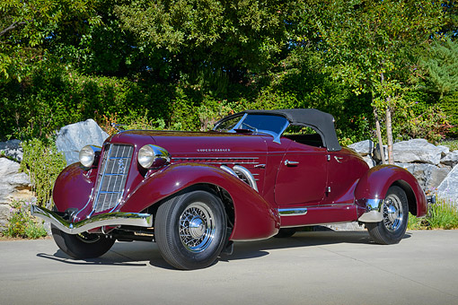 AUT 19 RK1097 01 © Kimball Stock 1936 Auburn 852 Speedster Maroon 3/4 Front View On Pavement By Trees