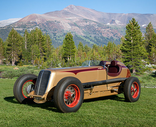 AUT 19 RK1104 01 © Kimball Stock 1937 Packard Indy Car Gold 3/4 Front View On Grass By Mountains