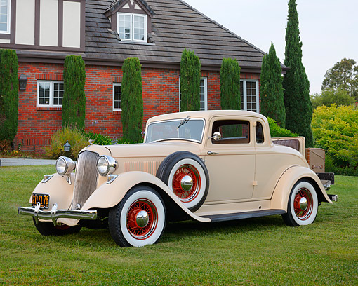AUT 19 RK1109 01 © Kimball Stock 1933 Plymouth PD Coupe Cream 3/4 Side View On Grass By Brick House