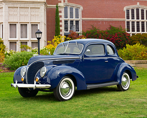 AUT 19 RK1115 01 © Kimball Stock 1938 Ford Deluxe 5-Window Coupe Blue 3/4 Front View On Grass By Building