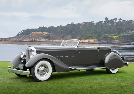 AUT 19 RK1123 01 © Kimball Stock 1934 Packard 1108 Twelve Dietrich Convertible Victoria Gray 3/4 Side View On Grass By Water Pebble Beach