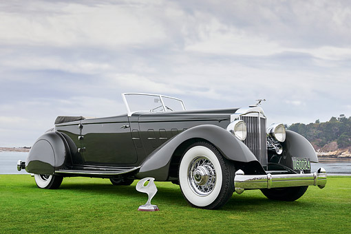 AUT 19 RK1126 01 © Kimball Stock 1934 Packard 1108 Twelve Dietrich Convertible Victoria Gray 3/4 Front View On Grass By Water Pebble Beach