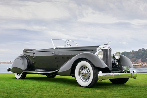 AUT 19 RK1127 01 © Kimball Stock 1934 Packard 1108 Twelve Dietrich Convertible Victoria Gray 3/4 Front View On Grass By Water Pebble Beach