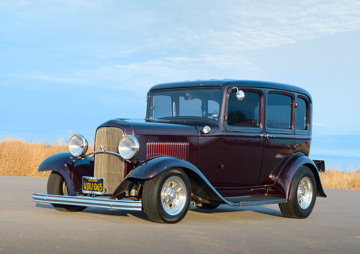 AUT 19 RK1134 01 © Kimball Stock 1930 Ford 4-Door Sedan Ice Cherry 3/4 Front View On Pavement By Field