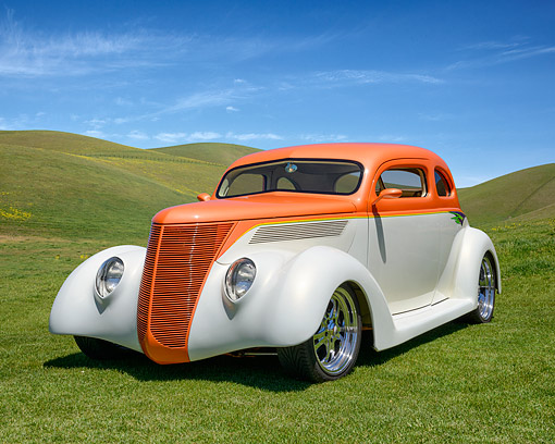 AUT 19 RK1137 01 © Kimball Stock 1937 Ford Coupe Custom Orange And White 3/4 Front View On Grassy Hills