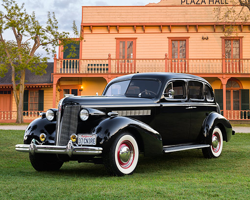 AUT 19 RK1162 01 © Kimball Stock 1937 Buick Black 3/4 Front View On Grass By Hotel