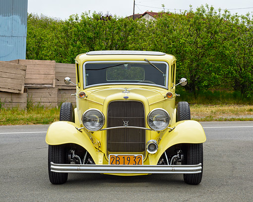 AUT 19 RK1173 01 © Kimball Stock 1932 Ford Sedan Delivery Truck Yellow Front View On Road By Trees