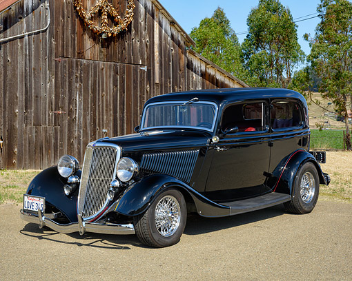 AUT 19 RK1187 01 © Kimball Stock 1934 Ford 2-Door Sedan Black 3/4 Front View By Barn