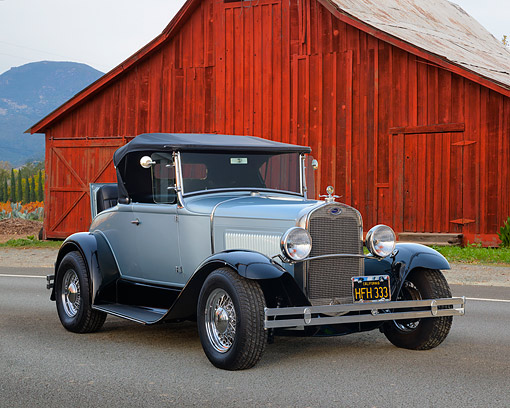 AUT 19 RK1195 01 © Kimball Stock 1930 Ford Model A Standard Roadster Coupe Light Blue With Black Trim 3/4 Front View By Barn