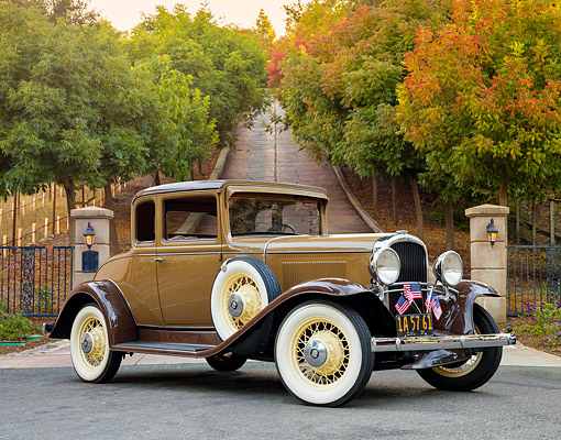 AUT 19 RK1198 01 © Kimball Stock 1931 Oldsmobile Deluxe Business Coupe Brown 3/4 Front View By Gate And Trees