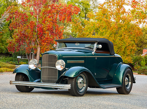 AUT 19 RK1204 01 © Kimball Stock 1932 Ford Roadster Green Custom Tires 3/4 Front View On Pavement By Trees