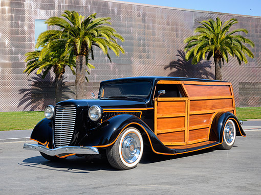 AUT 19 RK1217 01 © Kimball Stock 1930 Ford Woody Station Wagon Customized Black 3/4 Front View By Building And Palm Trees
