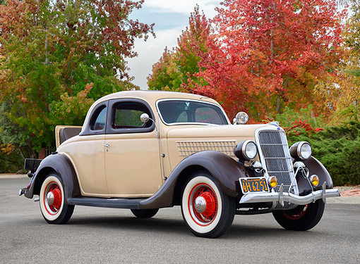 AUT 19 RK1222 01 © Kimball Stock 1935 Ford Model 48 5-Window Rumble Seat Coupe Creme 3/4 Front View Under Autumn Trees