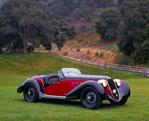 AUT 19 RK0098 02 © Kimball Stock 1939 Red And Black Alfa Romeo 6C 2500 Super Sport 3/4 Front On Grass By Fence And Trees Headlights On