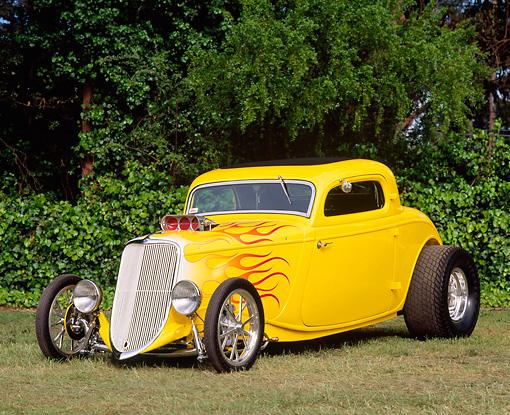 AUT 19 RK0176 01 © Kimball Stock 1933 Ford Coupe Yellow Hot Rod With Flames 3/4 Front View By Trees