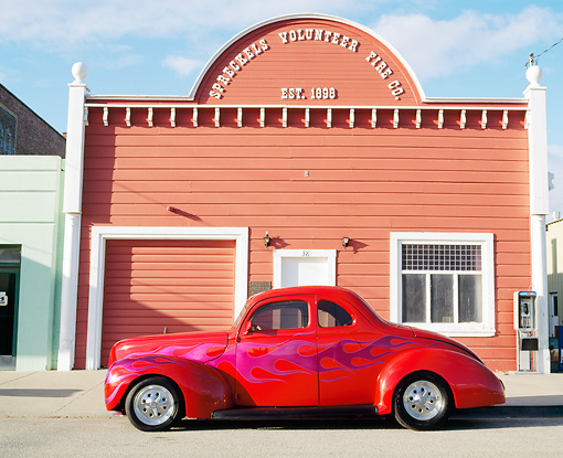 AUT 19 RK0186 02 © Kimball Stock 1939 Ford Coupe Red With Flames Hot Rod Profile View By Old Building