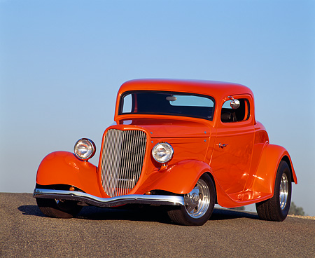 AUT 19 RK0199 03 © Kimball Stock 1934 Ford Custom Coupe Orange With Alien 3/4 Front View On Pavement Hill Blue Sky