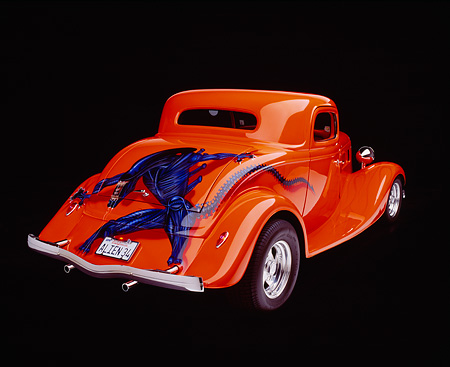 AUT 19 RK0204 16 © Kimball Stock 1934 Ford Custom Coupe  Orange With Alien 3/4 Rear View Studio