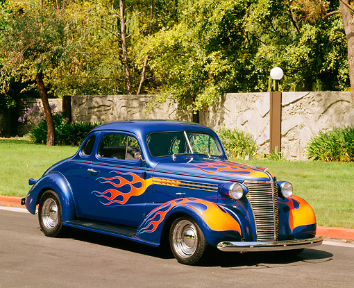 AUT 19 RK0229 04 © Kimball Stock 1938 Chevrolet Coupe Blue With Flames 3/4 Front View By Stone Wall Trees