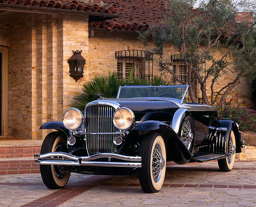 AUT 19 RK0251 05 © Kimball Stock 1930 Black Duesenberg (Murphy Body) 3/4 Front View On Driveway By House