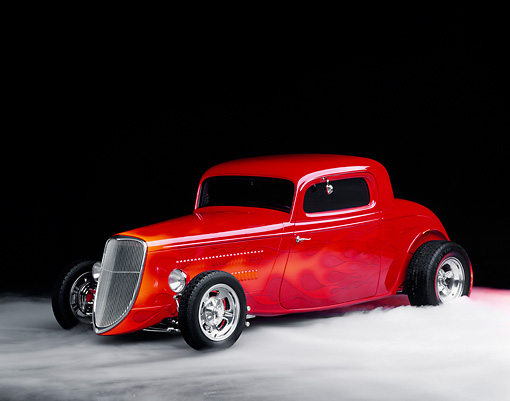 AUT 19 RK0289 11 © Kimball Stock 1934 Ford Coupe Red With Flames 3/4 Front View On Foggy Floor Studio