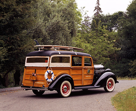 AUT 19 RK0327 01 © Kimball Stock 1936 Dodge Woody Westchester Suburban With Surfboard 3/4 Rear View By Trees