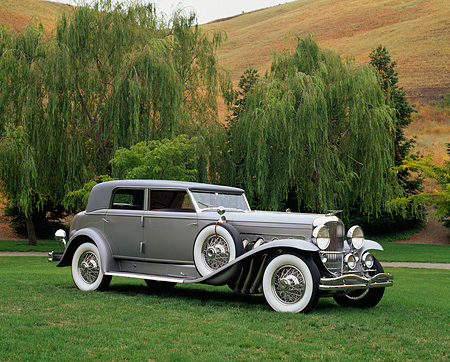 AUT 19 RK0339 04 © Kimball Stock 1934 Duesenberg Model J Rollston Sport Sedan Silver Side 3/4 View On Grass