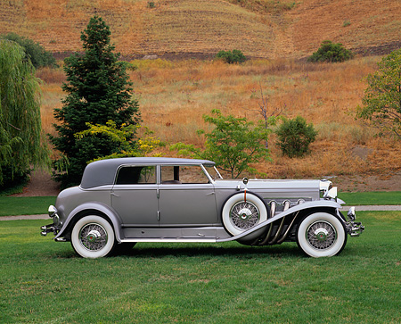 AUT 19 RK0340 01 © Kimball Stock 1934 Duesenberg Model J Rollston Sport Sedan Profile Silver Sedan On Grass