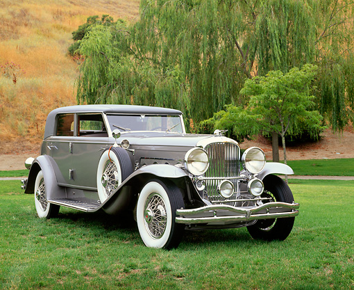 AUT 19 RK0341 01 © Kimball Stock 1934 Duesenberg Model J Rollston Sport Sedan Gray Front 3/4 View On Grass