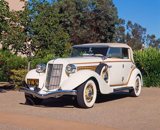 AUT 19 RK0368 03 © Kimball Stock 1935 Auburn Model 851 Phaeton Cream 3/4 Front View On Pavement By Mansion