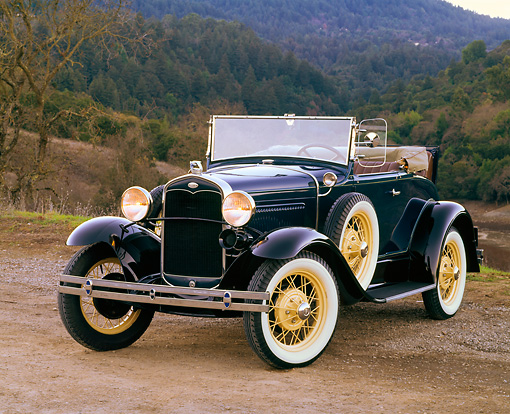 AUT 19 RK0401 01 © Kimball Stock 1931 Ford Model A Deluxe Roadster Blue 3/4 Front View On Dirt By Trees And Hills