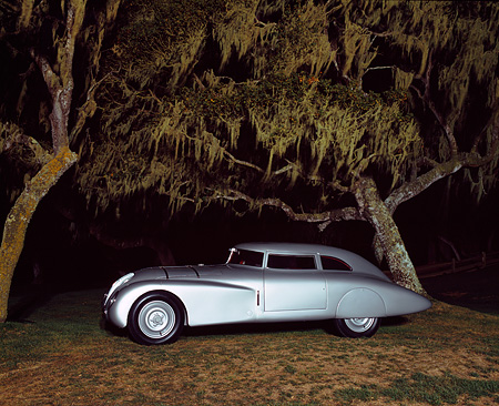 AUT 19 RK0427 03 © Kimball Stock 1937 Adler Rennlimousine Competition Coupe Silver 3/4 Side View On Grass By Trees At Night Pebble Beach