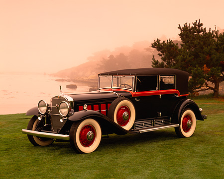 AUT 19 RK0430 01 © Kimball Stock 1930 Cadillac V16 Black And Red 3/4 Side View On Grass By Water Red Sky Pebble Beach
