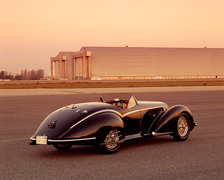 AUT 19 RK0500 02 © Kimball Stock 1937 Alfa Romeo 8C 2900B Spider Black 3/4 Rear View On Pavement Airplane Hangar Background
