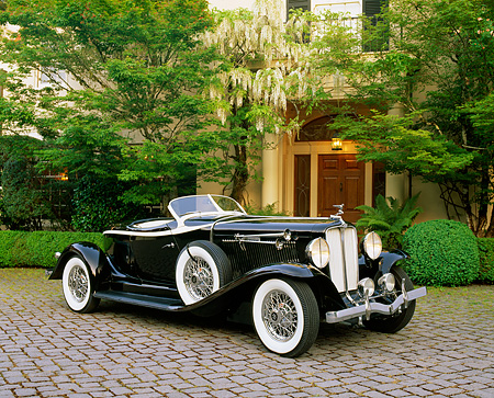 AUT 19 RK0505 03 © Kimball Stock 1933 Auburn V12 Boat-Tail Speedster Black 3/4 Side View On Pavement By Trees And Bushes