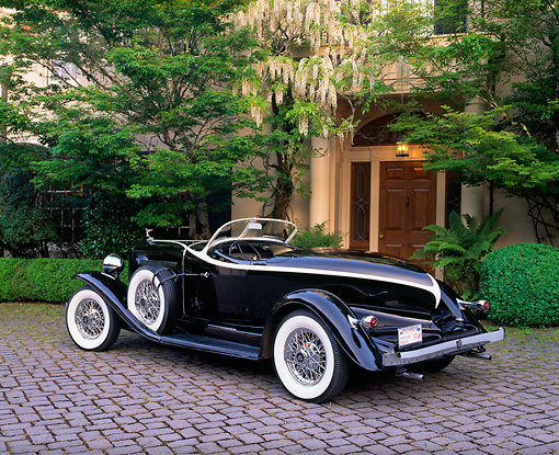 AUT 19 RK0507 03 © Kimball Stock 1933 Auburn V-12 Boat-tail Speedster Black 3/4 Rear View On Pavement By Trees And Bushes