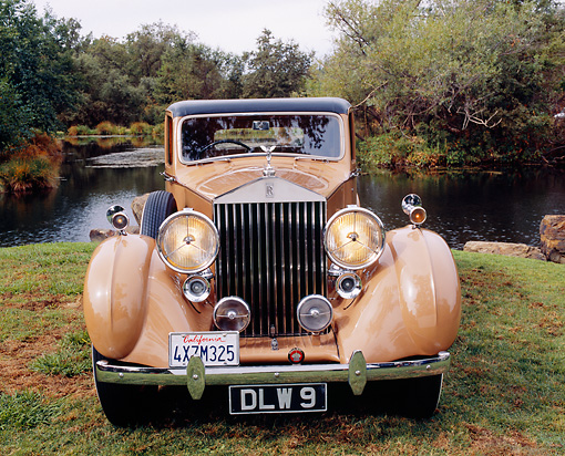 AUT 19 RK0563 01 © Kimball Stock 1937 Rolls Royce 25/30 Tan And Coffee Head On Shot On Grass By Water