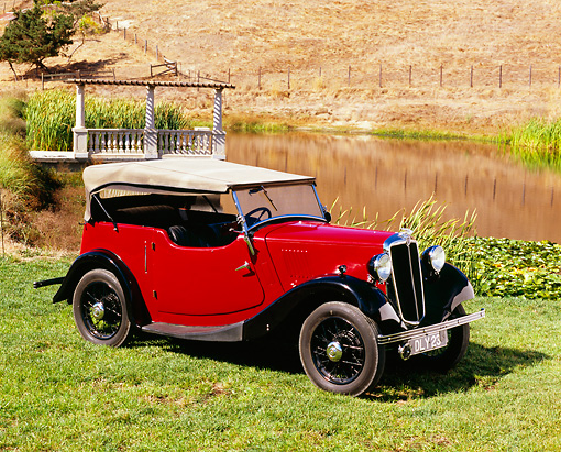 AUT 19 RK0597 03 © Kimball Stock 1937 Morris Eight Touring Convertible Burgundy And Black 3/4 Side View On Grass By Water