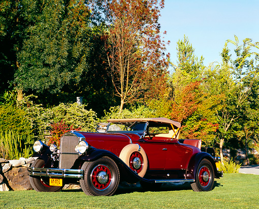 AUT 19 RK0599 01 © Kimball Stock 1930 Pierce-Arrow Model B Roadster Maroon 3/4 Front View On Grass By Rocks And Trees