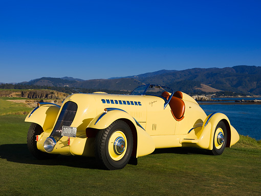 AUT 19 RK0669 01 © Kimball Stock 1935 Duesenberg SJ Speedster Yellow Front 3/4 On Grass Sky Water Mountain