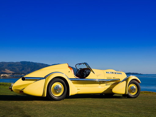 AUT 19 RK0671 01 © Kimball Stock 1935 Duesenberg SJ Speedster Yellow Rear 3/4 On Grass Sky Water Mountain
