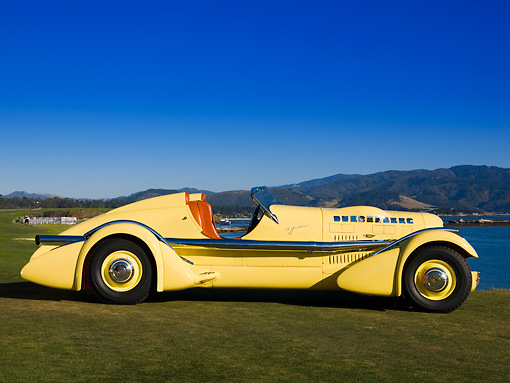 AUT 19 RK0672 01 © Kimball Stock 1935 Duesenberg SJ Speedster Yellow Profile On Grass Sky Water Mountain