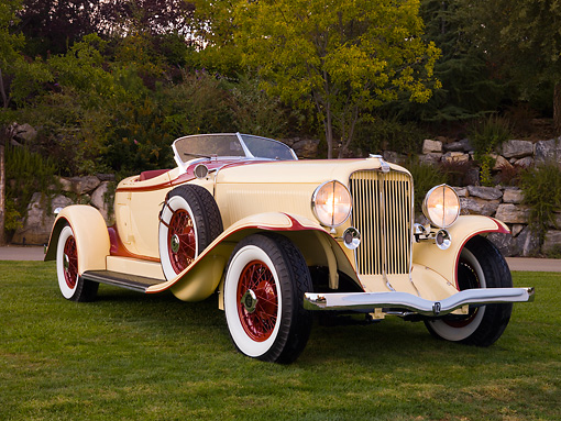 AUT 19 RK0687 01 © Kimball Stock 1932 Auburn V-12 Boattail Speedster 160 Yellow And Maroon Front 3/4 View On Grass By Trees