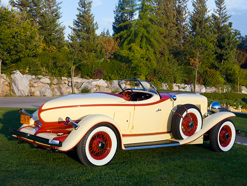 AUT 19 RK0688 01 © Kimball Stock 1932 Auburn V-12 Boattail Speedster 160 Yellow And Maroon Rear 3/4 View On Grass By Trees Wall Sky
