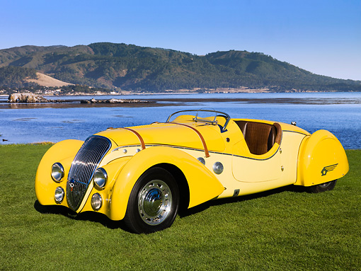 AUT 19 RK0691 01 © Kimball Stock 1938 Peugeot 402 Pourtout Darl'mat Roadster Yellow 3/4 Front View On Grass By Trees Building