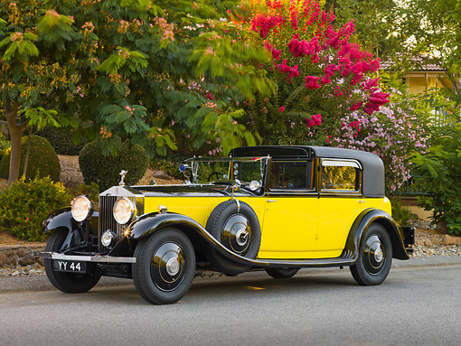 AUT 19 RK0703 01 © Kimball Stock 1931 Rolls-Royce Phantom II Yellow And Black 3/4 Front View On Pavement By Trees